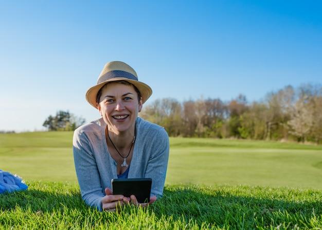 Vrouw camera kijken en glimlachen, die ebook in handen houden, liggend op groen gras in het park