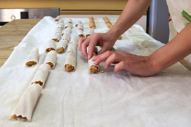 Vrouw cannelloni maken in haar keuken. thuis koken concept.
