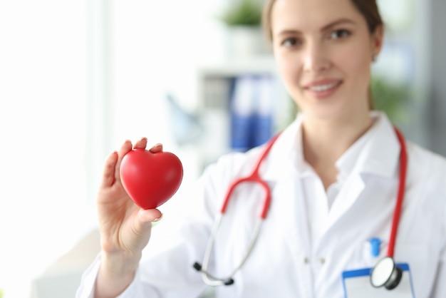 Vrouw cardioloog houdt klein rood hart in haar hand