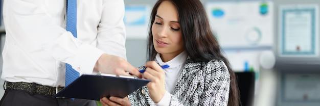 Vrouw ceo tekent zakelijk contract dat wordt tegengewerkt door haar werknemer