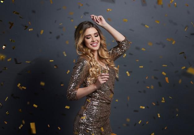 Vrouw champagne drinken en dansen onder de douche van confetti