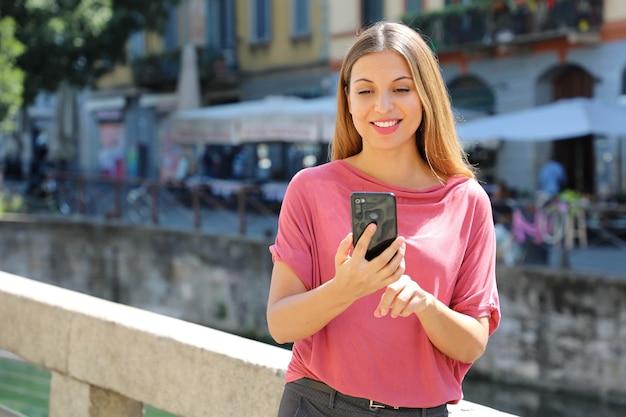 Vrouw chatten met mobiele telefoon op navigli-kanalen in milaan, italië
