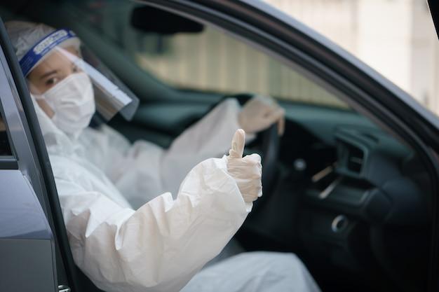 Vrouw chauffeur met handschoenen, beschermende hazmat pak, gelaatsscherm en masker. coronavirus of covid-19-bescherming.