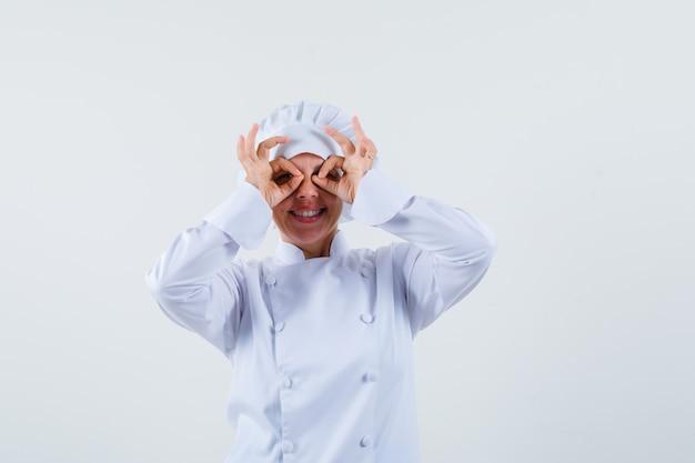 Vrouw chef-kok bril gebaar in wit uniform tonen en op zoek grappig.