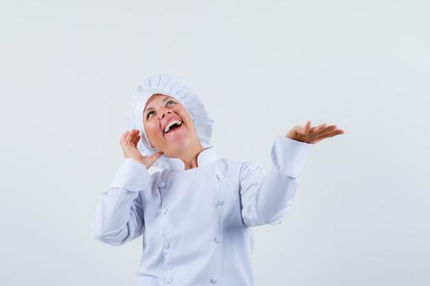 Vrouw chef-kok die zich voordeed als praten aan de telefoon terwijl de handpalm opzij wordt verspreid in wit uniform en er spraakzaam uitziet.