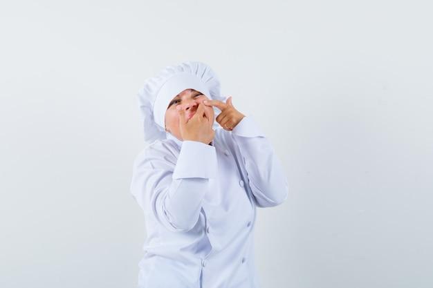 Vrouw chef-kok haar puistje op de wang in wit uniform knijpen