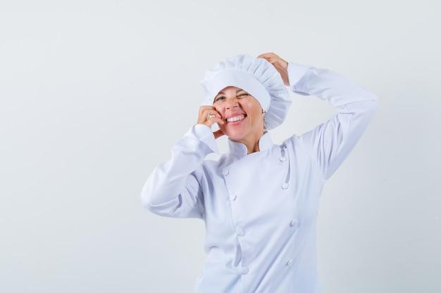 Vrouw chef-kok hand in hand op hoofd en wang in wit uniform en ziet er mooi uit.
