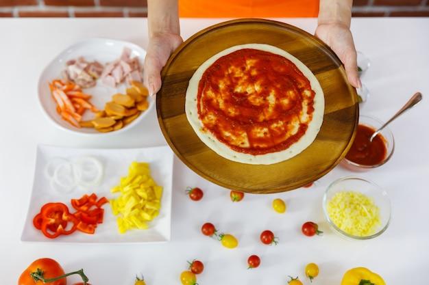 Vrouw chef-kok in oranje schort bereidt zich voor om smakelijke gezonde pizza te koken op houten plaat met verscheidenheid aan verse rode en gele tomaten, vlees, biologische ingrediënten en kruiden op witte tafel in de buurt van bakstenen muur