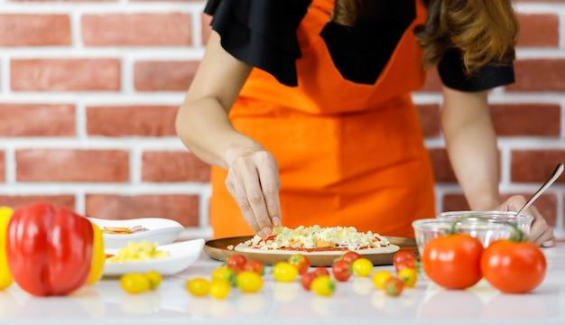 Vrouw chef-kok in oranje schort geconcentreerd koken in de buurt van bakstenen muur en zorgvuldig gieten topping op schotel van gezonde biologische voeding gemaakt door verscheidenheid van rode en gele tomaten op tafel van thuis keuken