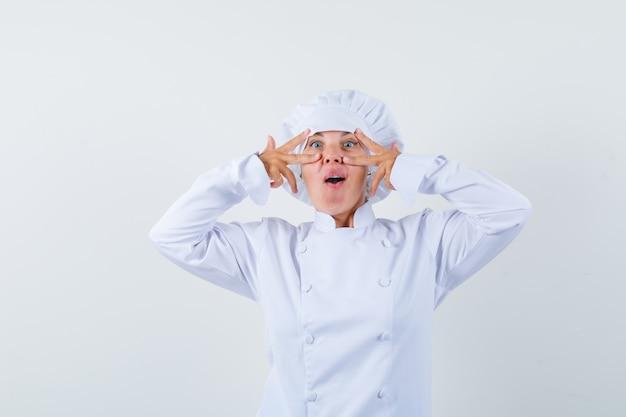 Vrouw chef-kok in wit uniform overwinning gebaar tonen op ogen en verbaasd kijken