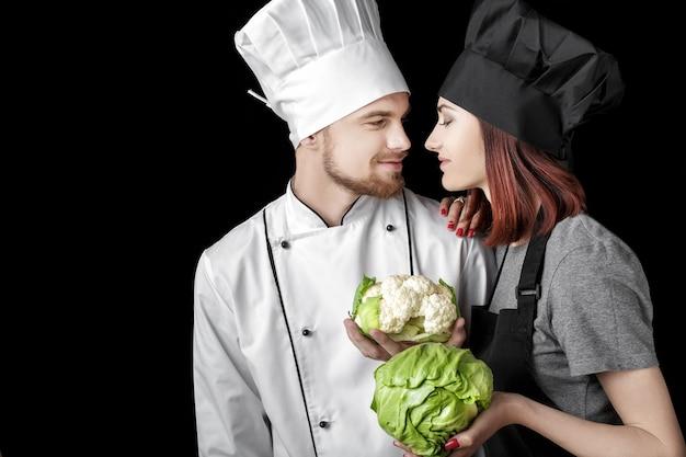 Vrouw chef-kok in zwart uniform en man chef-kok in wit uniform houden verse groene kool en bloemkool o...