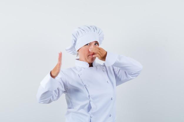Vrouw chef-kok knijpen neus als gevolg van slechte geur in wit uniform en walgt op zoek