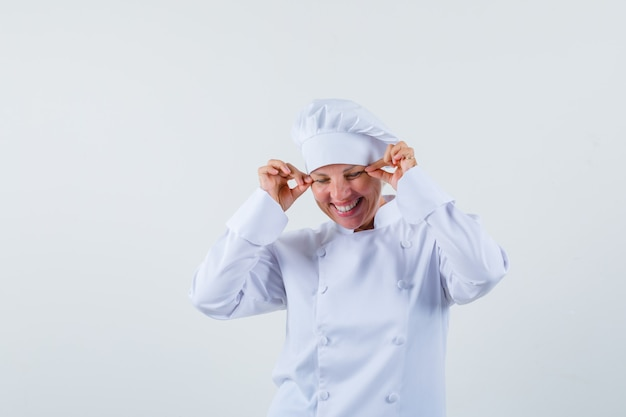 Vrouw chef-kok knijpt haar oogleden in wit uniform en ziet er gek uit.