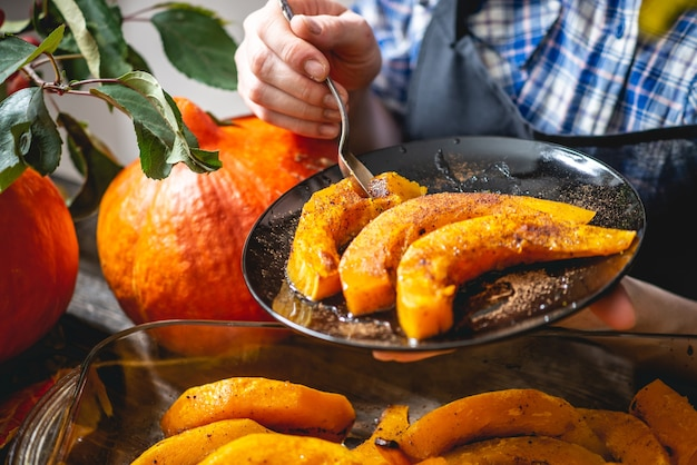 Vrouw chef-kok met plakjes gebakken oranje pompoen met honing en kaneel