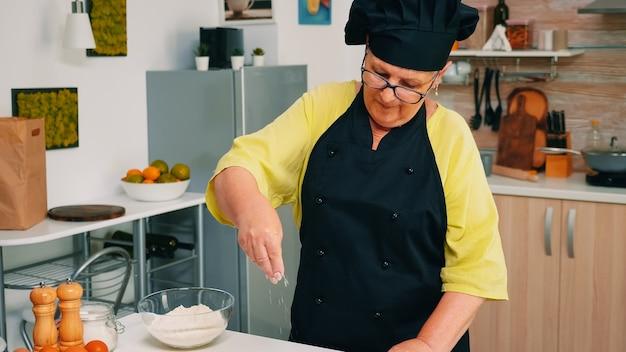 Vrouw chef-kok tarwebloem uit glazen kom nemen en zeven op tafel. gepensioneerde senior bakker met bonete en uniform besprenkelen, zeven, verspreiden van nieuwe ingrediënten die zelfgemaakte pizza en brood bakken.
