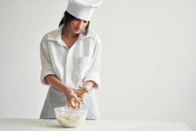 Vrouw chef-kok uniform werkt met deegmeelproducten koken voedsel