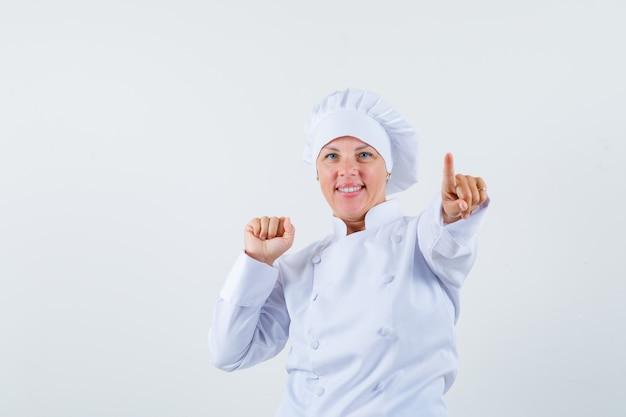 Vrouw chef wijst naar voren terwijl ze haar vuist in wit uniform toont