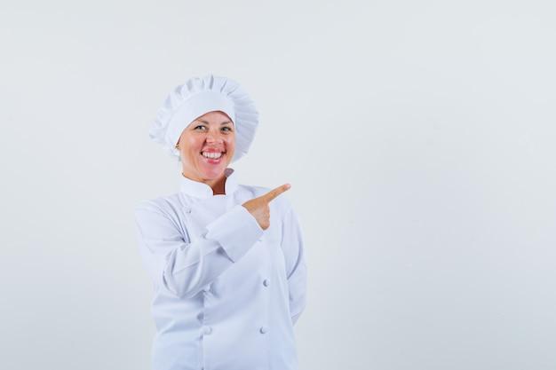 Vrouw chef wijst opzij in wit uniform en ziet er vrolijk uit