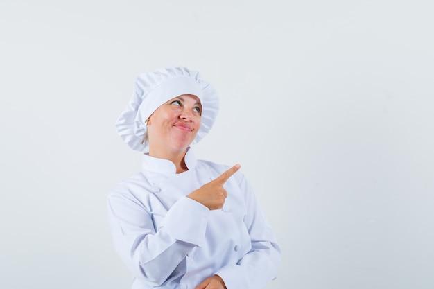 Vrouw chef wijzend op de rechterbovenhoek in wit uniform en aarzelend op zoek