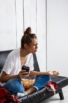 Vrouw chips eten, frisdrank drinken, tv kijken, zittend op de bank.