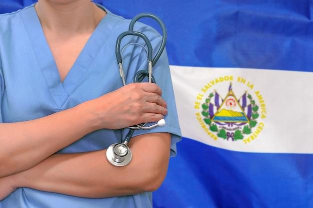 Vrouw chirurg of arts met een stethoscoop op de achtergrond van de vlag van el salvador