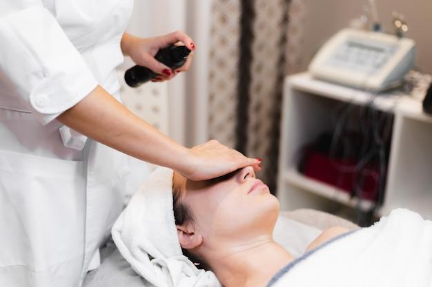 Vrouw cliënt in salon handmatige gezichtsmassage ontvangen schoonheidsspecialiste