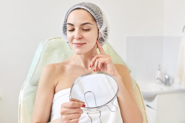 Vrouw cliënt van cosmetologie salon tevreden met resultaat van cosmetische procedure.