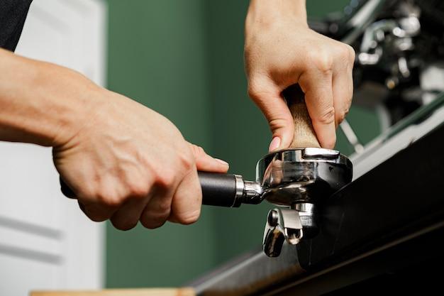 Vrouw coffeeshop werknemer koffie op professionele koffiemachine voorbereiden