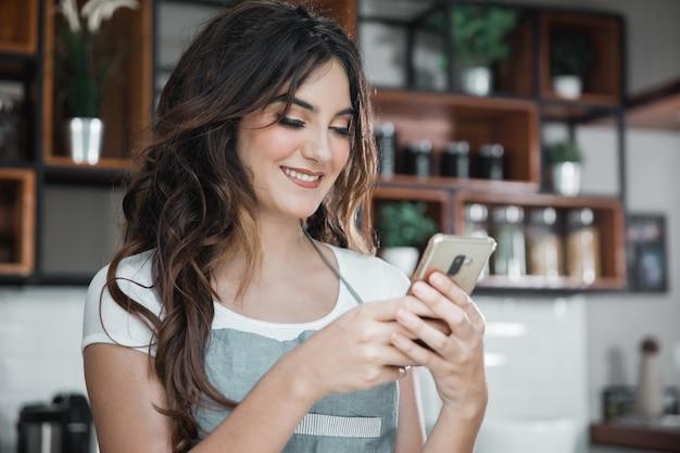Vrouw coffeeshop werknemer met smartphone