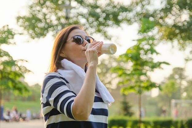 Vrouw consumptiemelk van middelbare leeftijd, zuivelproduct, yoghurt uit de fles