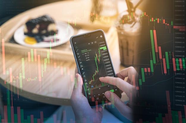 Vrouw controleert bitcoin-prijsgrafiek op digitale uitwisseling op smartphone in het café