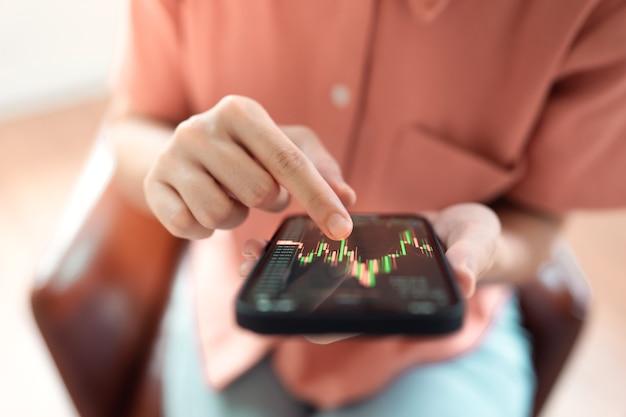 Vrouw controleert bitcoin-prijsgrafiek op digitale uitwisseling op smartphone