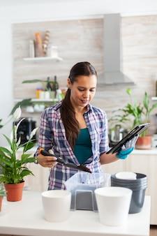 Vrouw controleert grond op bloemen tijdens het tuinieren en houdt tablet pc vast