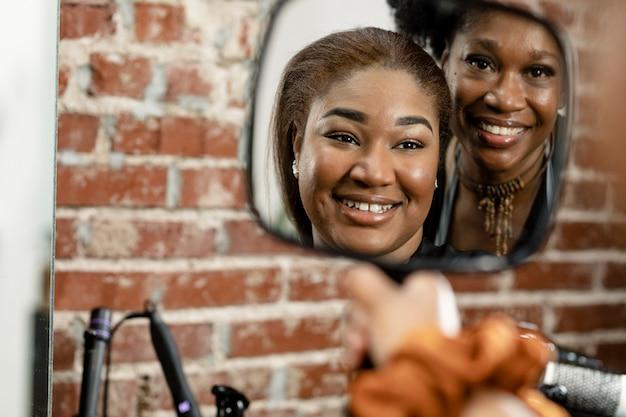 Vrouw controleert haar nieuwe kapsel in een spiegel