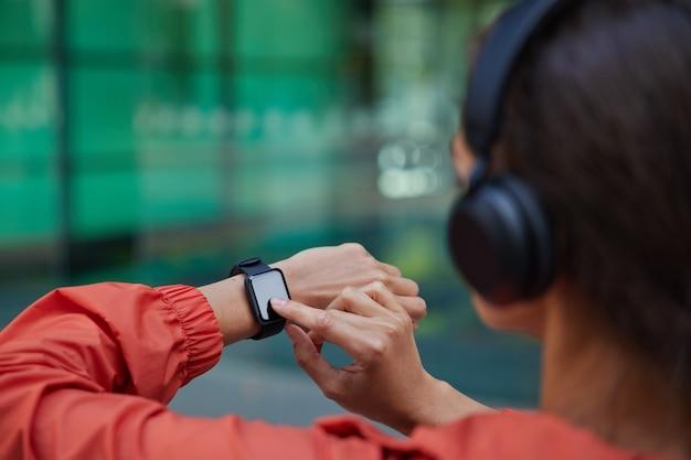 Vrouw controleert resultaten van fitnesstraining op smartwatch luistert muziek via koptelefoon gekleed in anorak poses op wazig