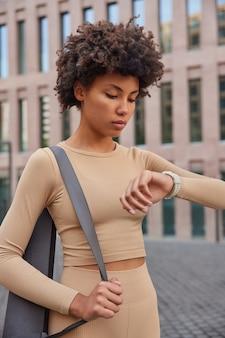 Vrouw controleert tijd op smartwatch na cardiotraining gaat pilates trainen gekleed in beige trainingspak wandelen in stedelijke omgeving