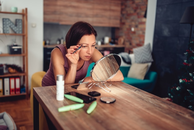 Vrouw corrigeren wenkbrauwen vorm met een pincet