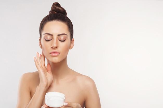 Vrouw cosmetica crème toe te passen en glimlachen. mooi gezicht. lichaamsverzorging. huidsverzorging.