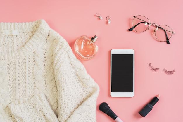Vrouw cosmetica en mode items met smartphone en kopie ruimte, bovenaanzicht