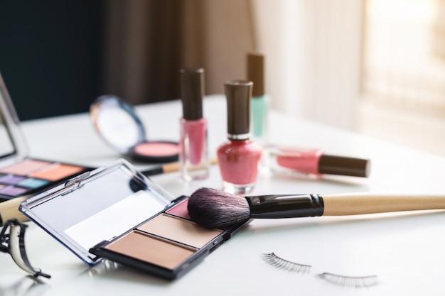 Vrouw cosmetica, penseel en make-up op kaptafel thuis