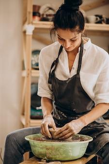 Vrouw craftmaster bij een aardewerkwinkel