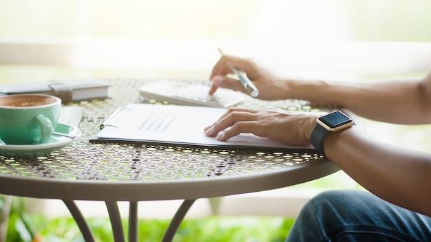 Vrouw creatieve bedrijf met behulp van calculator op een terrasje