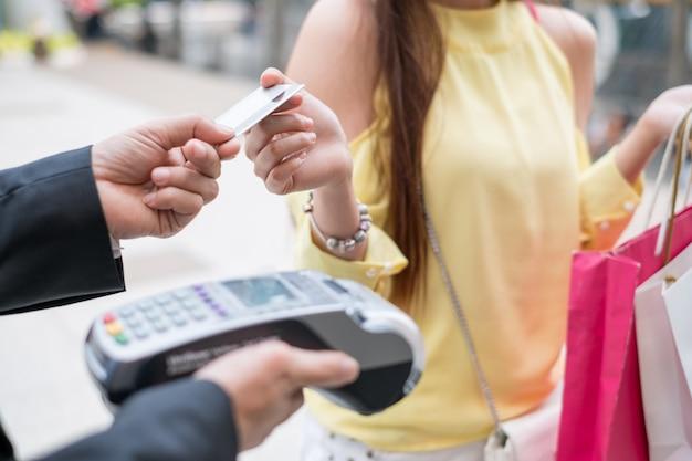 Vrouw creditcard betalen met betaalterminal met kassier man