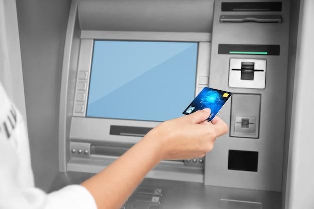 Vrouw creditcard invoegen in geldautomaat, close-up