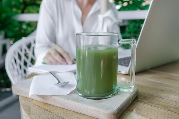 Vrouw cup groene matcha latte koffie thee glas werkplek cafe terassa huis freelancer