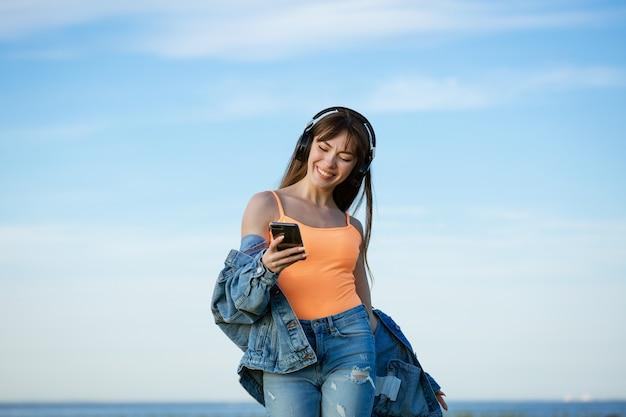 Vrouw dansen en zingen op muziek op een koptelefoon op het strand