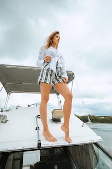 Vrouw dansen staande op de neus van het jacht op een zonnige zomerdag, wind haar ontwikkelen. samen plezier maken en genieten van de zon tijdens het zeilen op zee. reizen en zeilen concept.