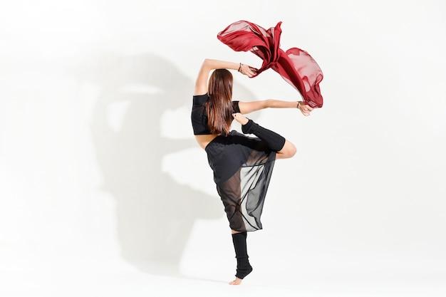 Vrouw danser uitvoeren van een alternatieve arabesque dans pose sierlijk flicking rode stof boven haar hoofd in een achteraanzicht over wit met schaduw en copyspace