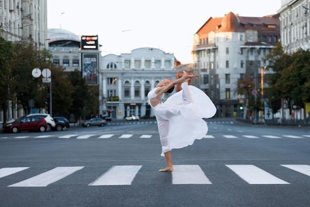 Vrouw danseres op de weg in de stad bij dageraad