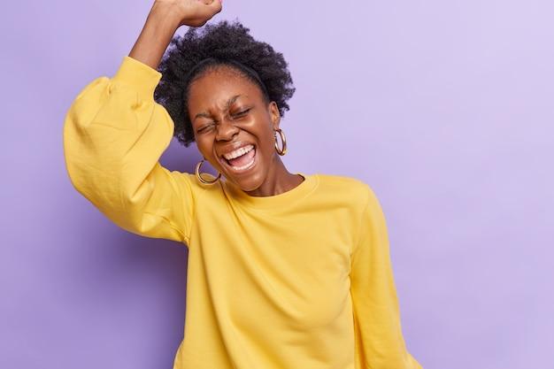 Vrouw danst met vreugde houdt arm omhoog roept vrolijk iets vierend gekleed in casual gele trui geïsoleerd op paars